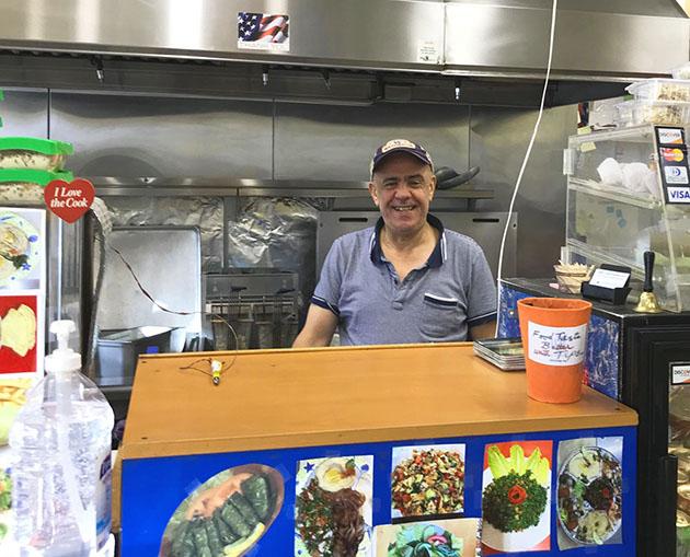 Samir Alawar standing behind the counter