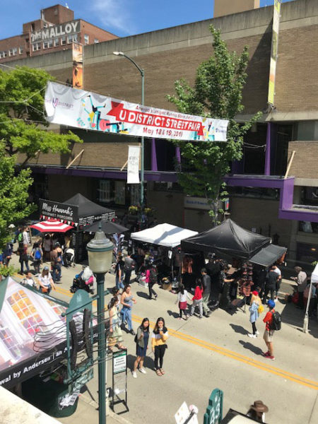 Photo looking down on University Way with a banner stating University District StreetFair